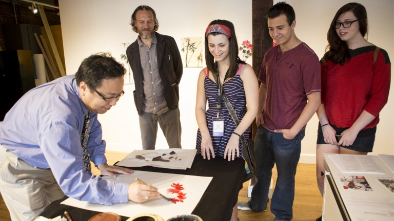 A SCAD professor demonstrates a painting technique during SCAD Day