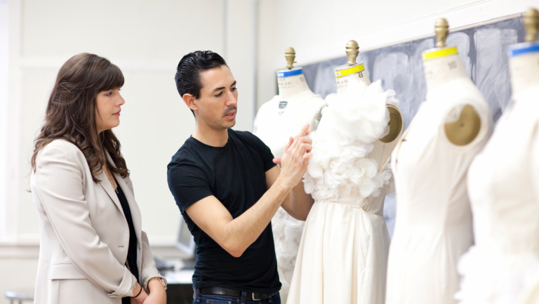 Fashion mentor Christian Cota critiquing student designs