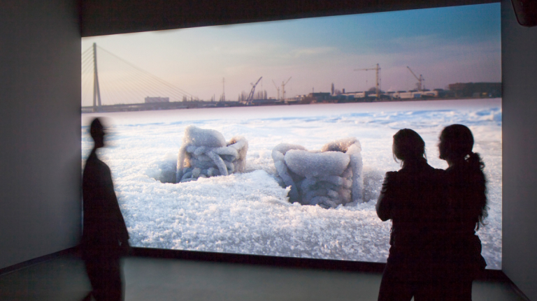 Gallery attendees viewing video installation by Sigalit Landau