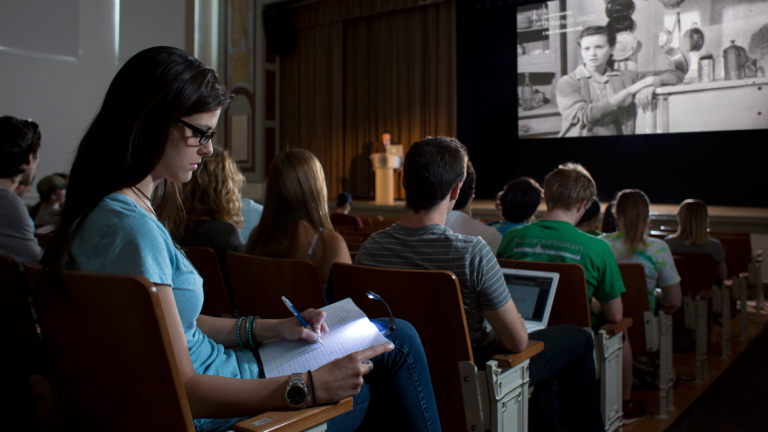 Cinema studies student taking notes during film lecture