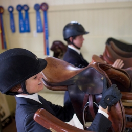 Equestrian students storing saddles in tack room