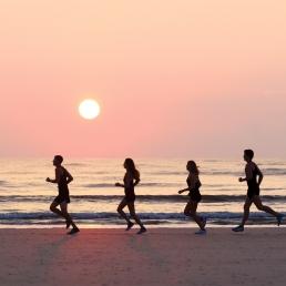 SCAD cross country athletes run across beach at sunset