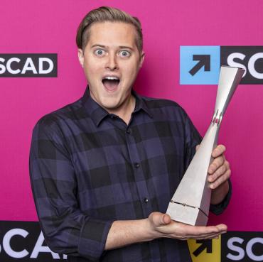 Lucas Grabeel holding trophy