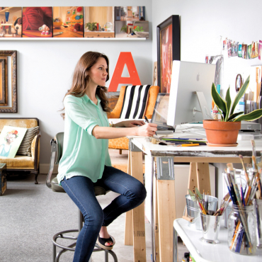 eLearning student sitting at desk in painting studio