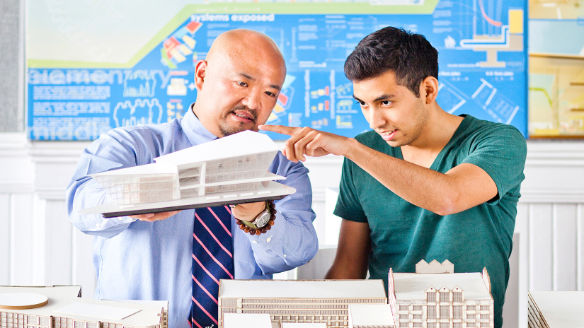 Architecture professor examining model with student